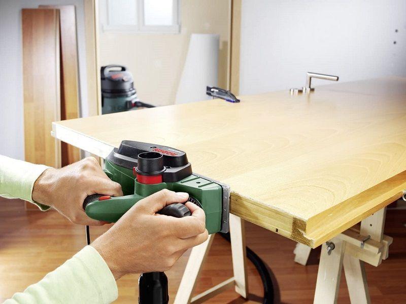 cepillo eléctrico para madera cepillando una puerta